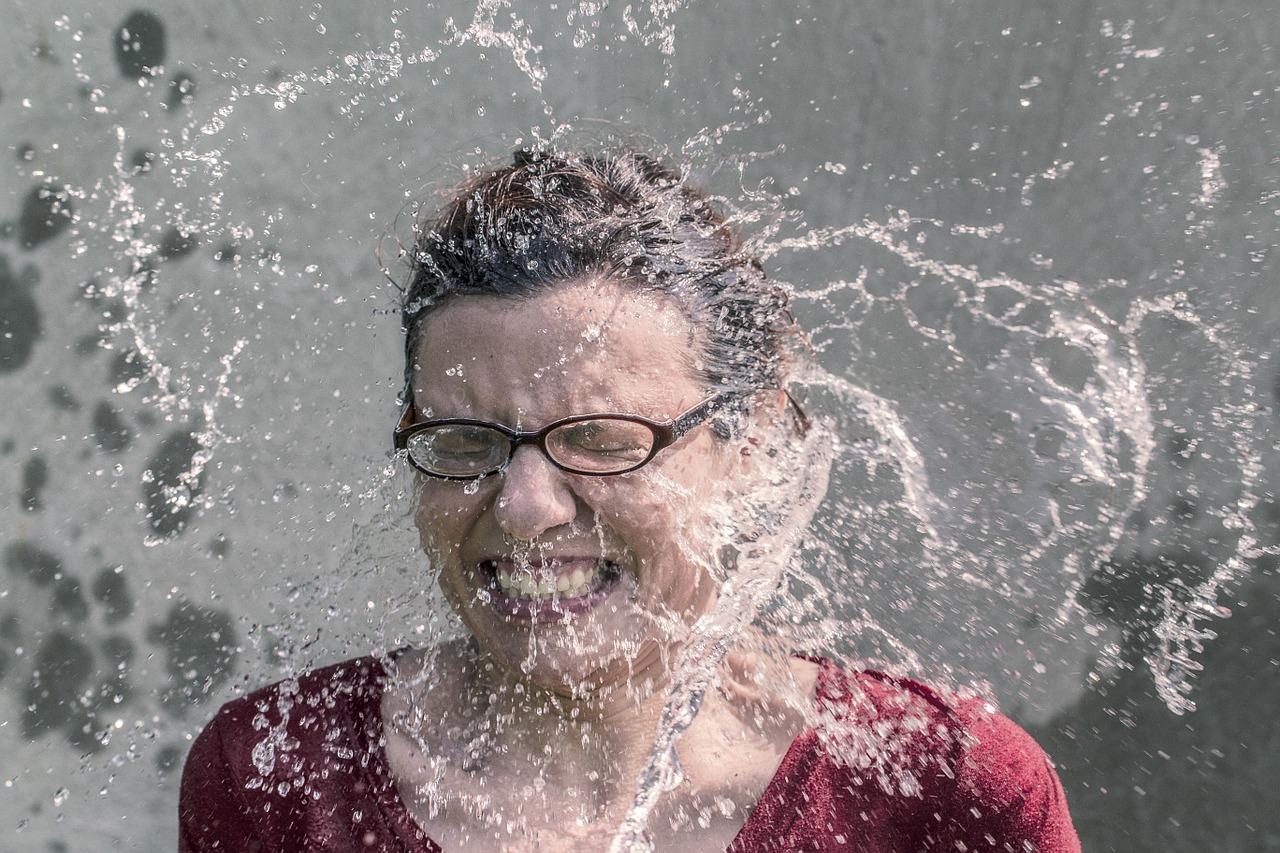 顔に水を浴びている女性